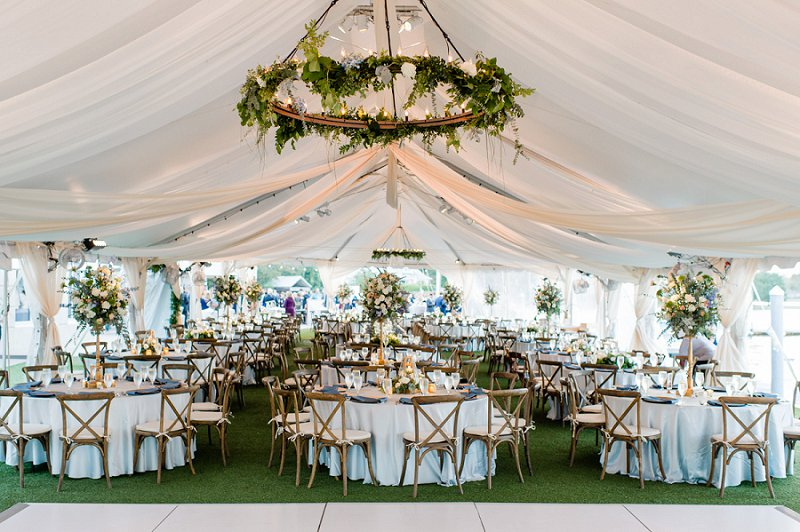 Elegant outdoor wedding tent with drapery and greenery chandeliers for a romantic wedding under the stars