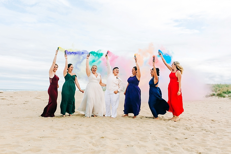 Wedding party with rainbow smoke bombs for awesome beach wedding idea