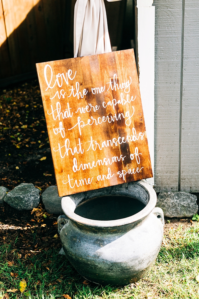 Pretty handlettered wooden wedding sign with a love quote