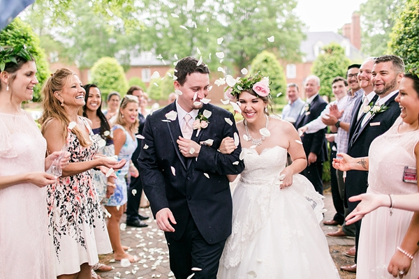 Happy wedding couple being greeted with rose petals