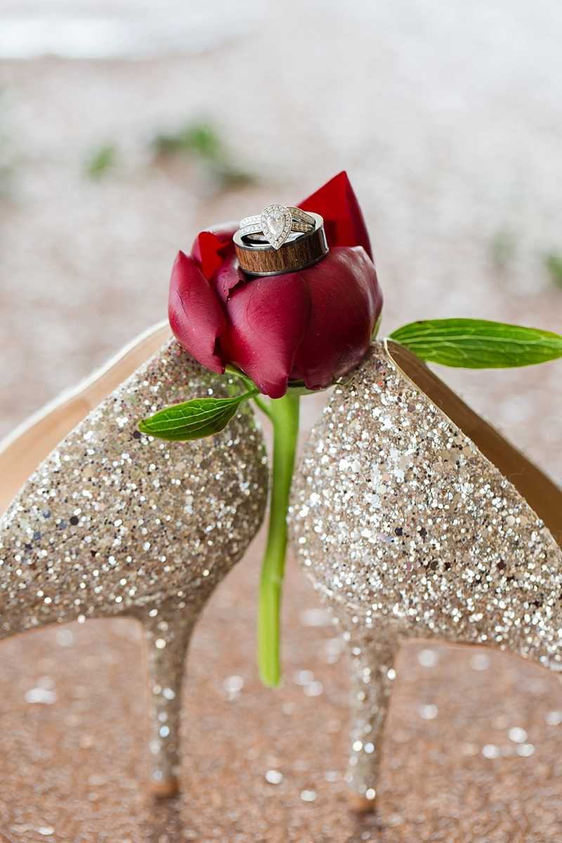 Wedding ring shot with sparkly gold bridal shoes and red flower