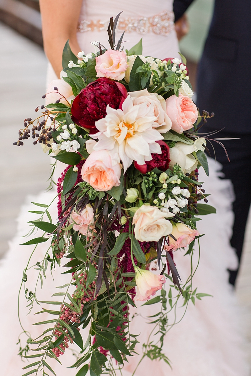 Gorgeous cascading wedding bouquet with red peonies and garden roses with magenta pink amaranthus