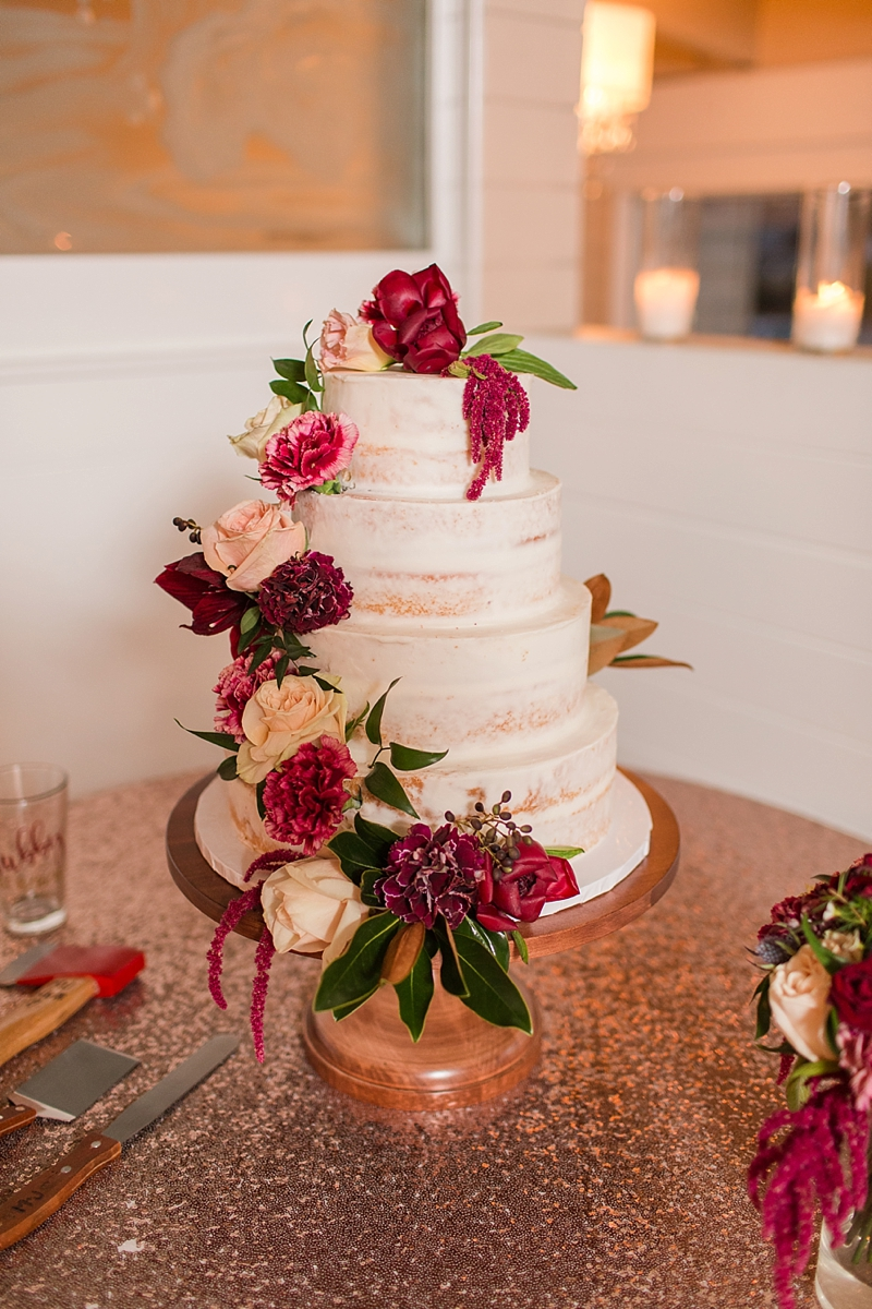 Simple semi naked wedding cake with textured red and pink flowers