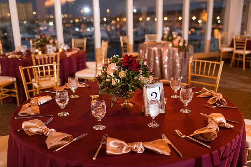 Dark red and gold evening wedding reception table with framed table numbers