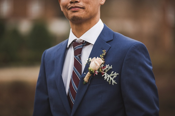 Navy blue suit and oxblood tie for groom