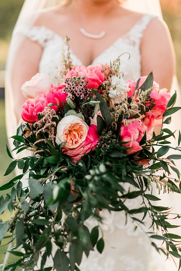 Colorful wedding bouquet with greenery and large bright pink coral charm peonies