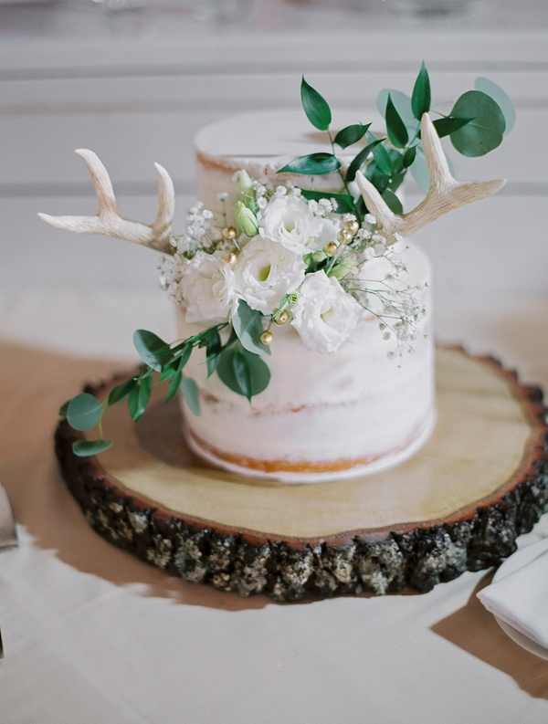 Mini semi naked wedding cake with eucalyptus and antlers on a wood slab