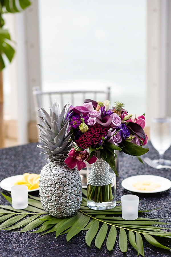 Silver pineapple wedding centerpiece with purple tropical flowers and greenery