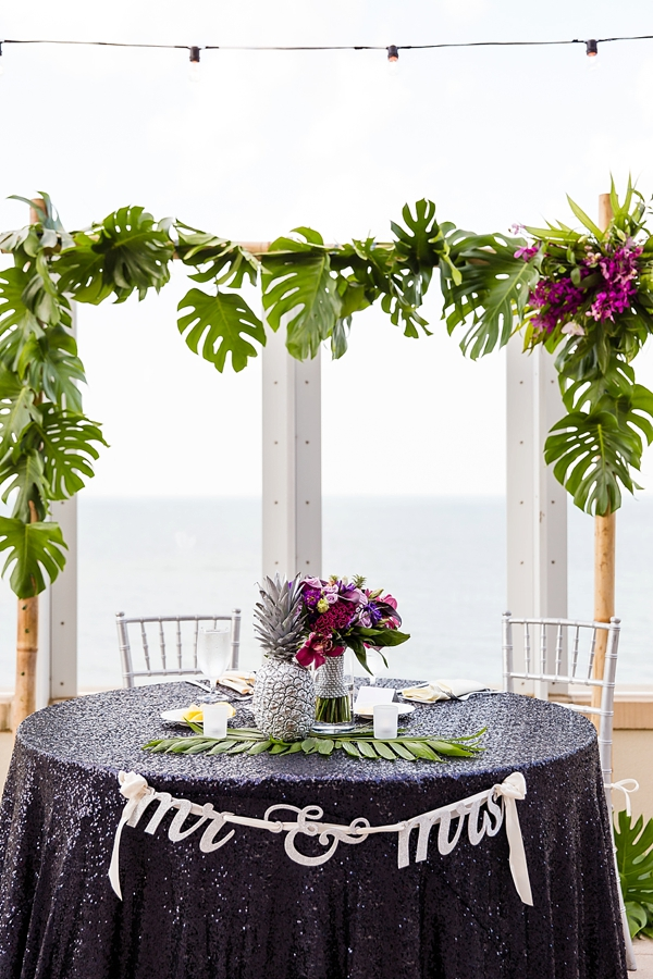 Tropical sweetheart table with bamboo arch and navy blue sequin tablecloth