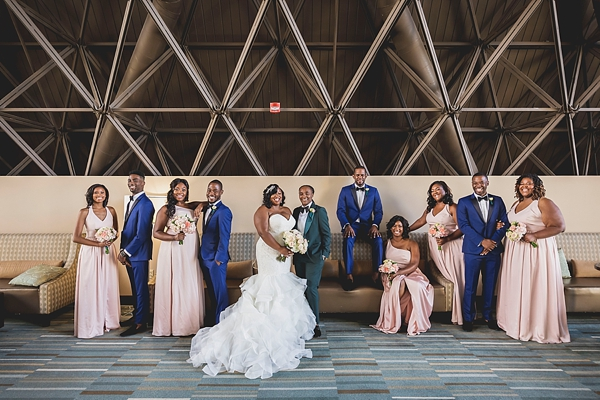 Wedding party in blush dresses and blue tuxedos