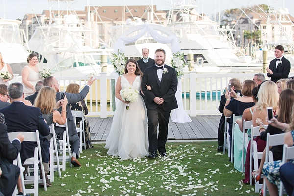Beautiful waterside wedding ceremony with white flowers