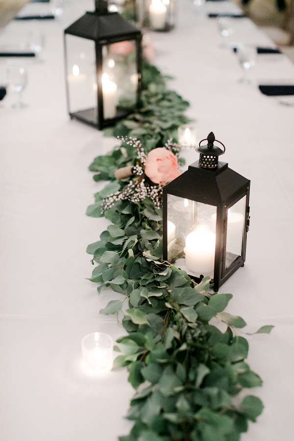 Black lanterns for winter wedding centerpieces and greenery table runner
