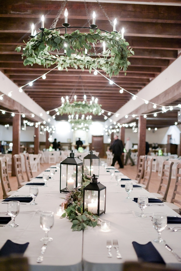 Greenery wreaths on chandeliers and twinkling bistro lights for winter wedding
