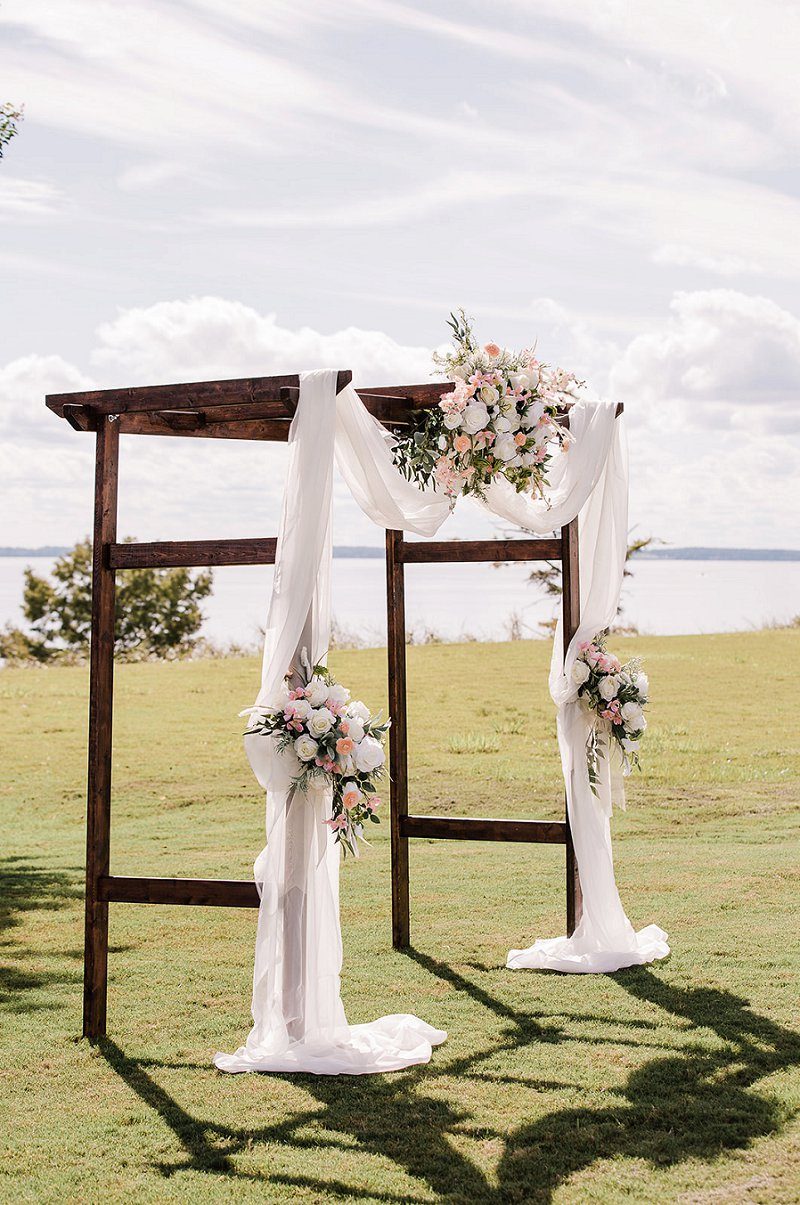 Handmade wooden wedding arch with white drapery and a gorgeous floral spray
