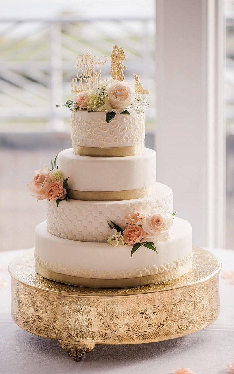 Whimsical gold and white wedding cake with custom sparkly gold cake topper