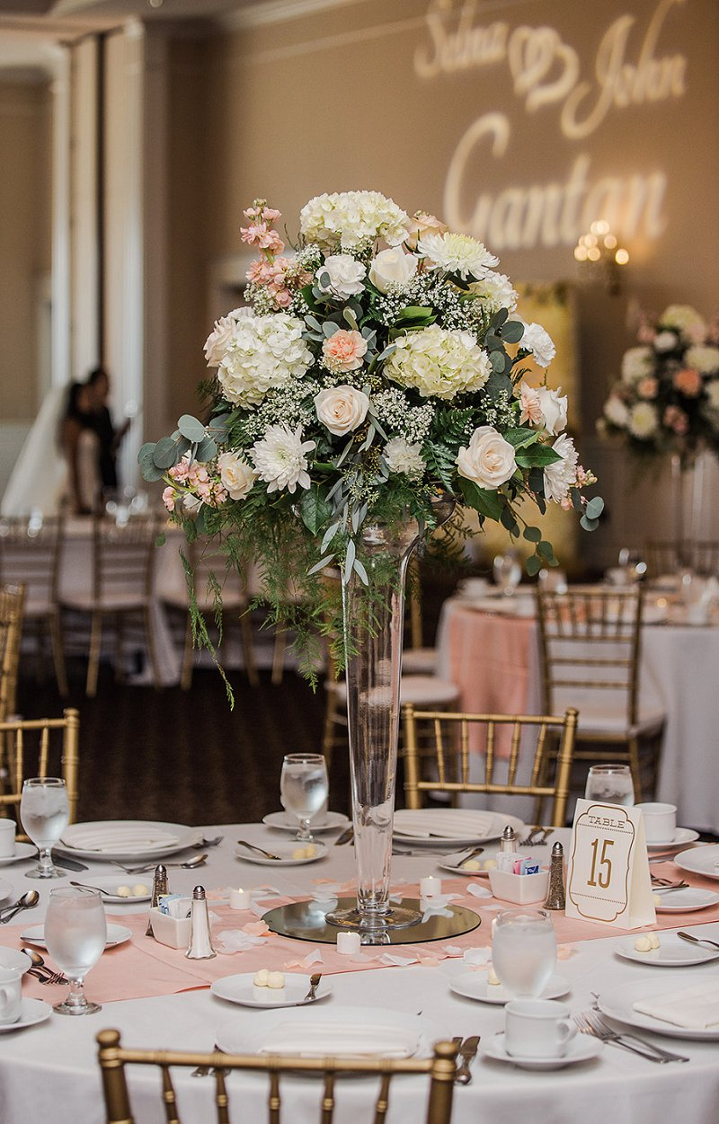Tall glass floral centerpiece with white and pink flowers spilling over