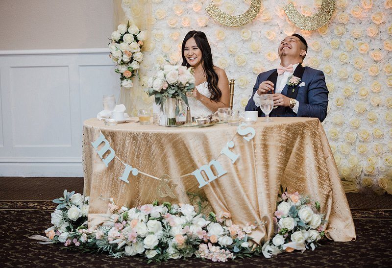 Handmade gold and white flower backdrop for sweetheart table in ballroom wedding reception