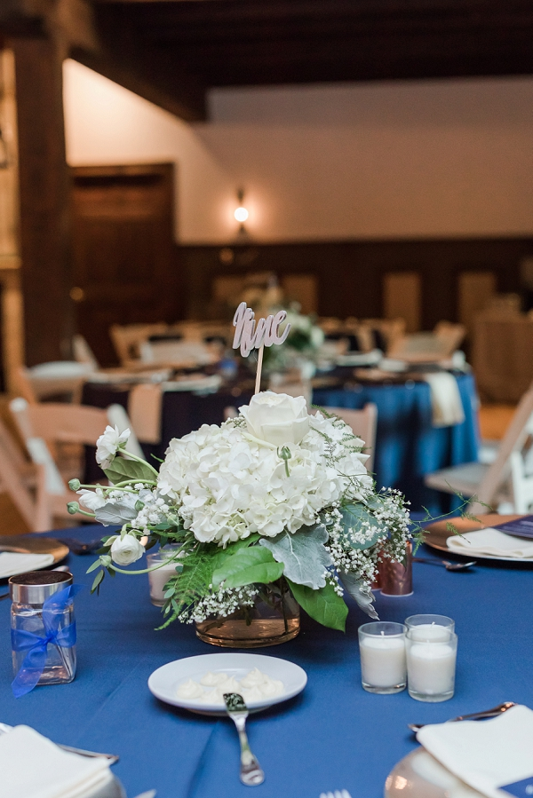 White hydrangea wedding centerpiece with silver table number pick