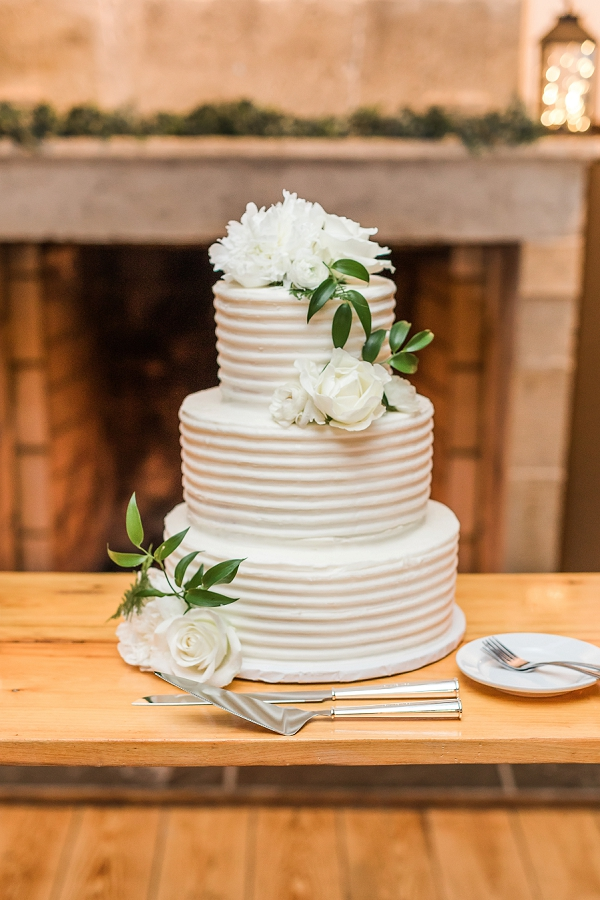 Textured white wedding cake with simple white flowers and ridges