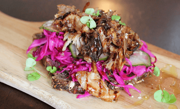Pulled pork Smørrebrød with pickled cabbage and salted cucumbers