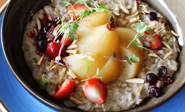 Power seed almond milk porridge with toasted nuts, vanilla poached pear and berries