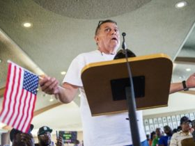 Flint resident Keith Pemberton, with an American flag, speaks his three-minute limit during a special Flint City Council meeting in City Hall in Flint, Mich., Wednesday, May 17, 2017. About 22 percent of excavations tied to Flint's lead-tainted water crisis have led to copper pipes that do not pose a threat of leaching lead, city records show. (Jake May/The Flint Journal-MLive.com via AP)