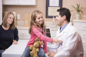 Child holding a stethoscope up to doctors chest while laughing