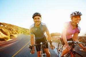 Man and woman road biking on a mountain road