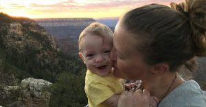 Mother kissing her baby with oxygen tubs in his nose in the mountains during sunset