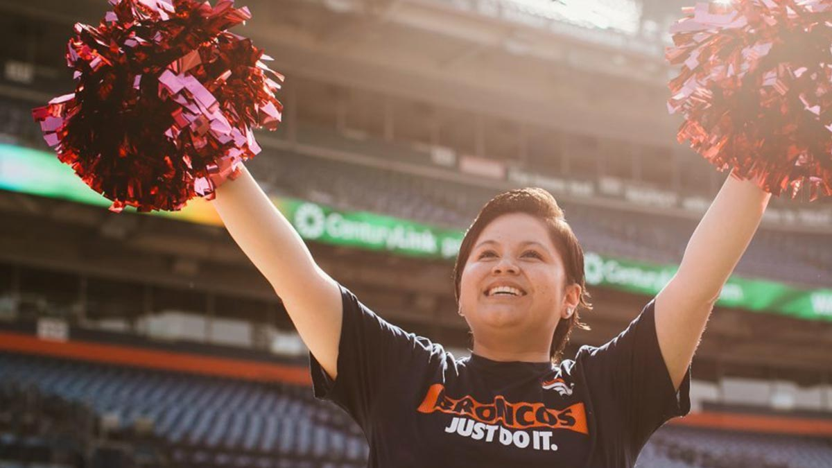 Teenager playing the role of a Denver Broncos cheerleader