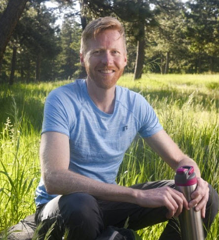 Outdoorsman Jonathan Proctor sitting in a mountain meadow