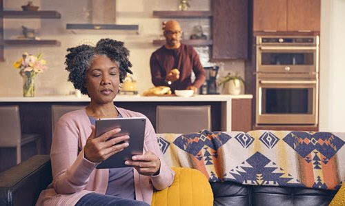 Woman on couch looking at tablet screen