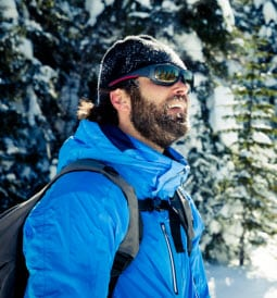 man hiking in snowy forest