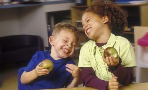 A young boy and girl giggle while eating green apples.