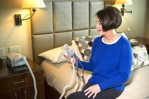 "Anita Kitt, one of UCHealth's first patients to be implanted with an Inspire device to treat her sleep apnea, looks at a CPAP machine, which she used to call, ""the monster under my bed."""