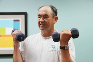man lifts weights as part of a program that UCHealth provides the school district, one of the ways to reduce health care costs.