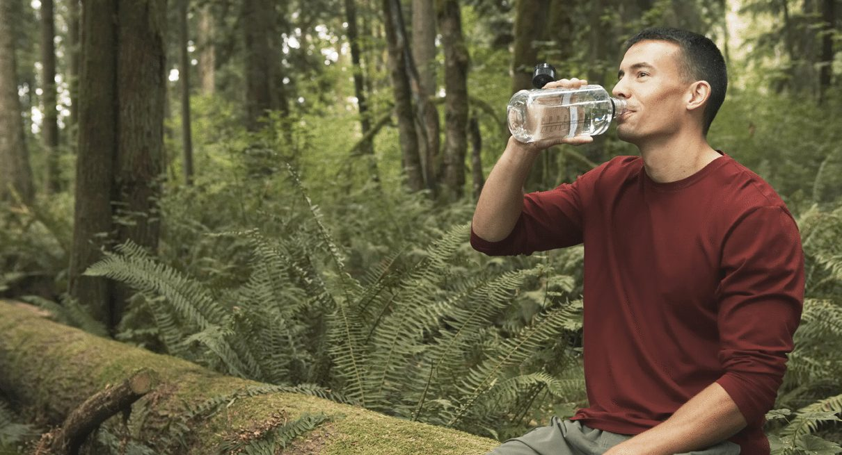 man drinks water in the woods