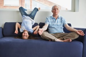an older person does yoga on a couch while a child does a headstand next to him