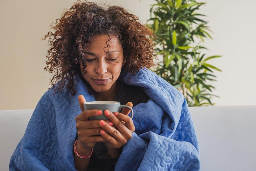 woman feeling sick and drinking tea