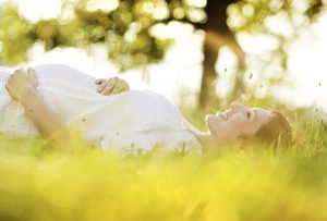 a pregnant woman lays on her back in the grass