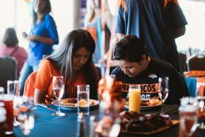 Carmen and Anna briefly pray at champagne brunch hosted by the Broncos as part of the Salute to Survivors event.