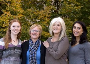 Four women who are working to prevent skin cancer pose side by side in front of a tree.