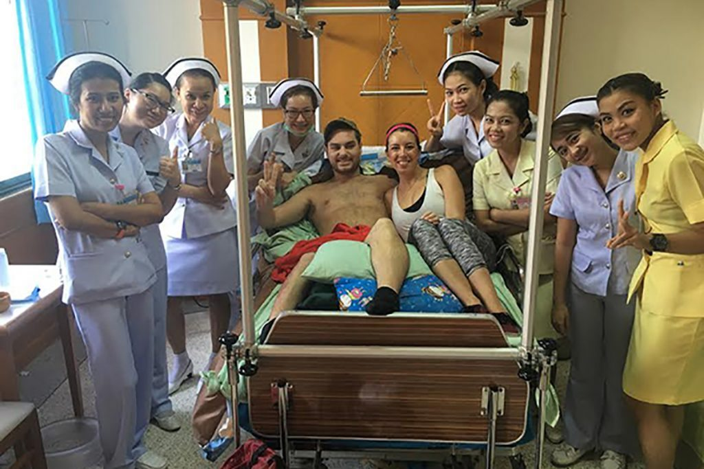 A patient and his wife pose in a hospital bed in Thailand. They are surrounded by their nurses.