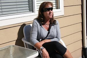 A blind woman sits outside her home. She now has a bionic eye and uses it to find her way around her home.