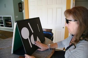 A patient uses a magnetic board to practice using the bionic eye.