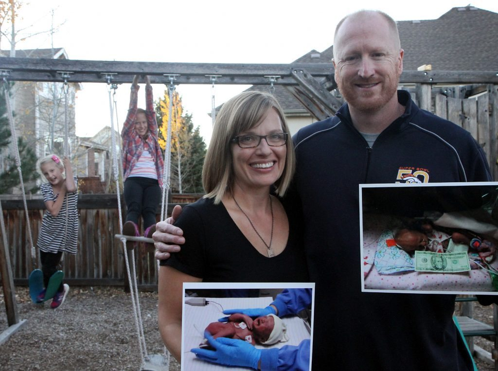 Steve Armstrong (right) and his wife, Melissa, hold up photos of their girls who were born prematurely at Poudre Valley Hospital. The girls, Maya (back right), now 11, and Sofia (back left), 8, are happy, healthy kids. Photo by Kati Blocker, UCHealth.