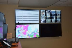 A monitor in the transfer center displays a weather map, live views of ambulance bays at UCHealth hospitals, and the ED status of hospitals in the Denver metro area and other regions.