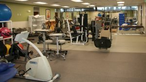 a gym with workout bikes and weights