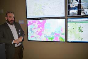 Senior DocLine Director Rob Leeret stands near four screens DocLine