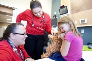 ER staff talk with a girl holding a cheta stuffed animal